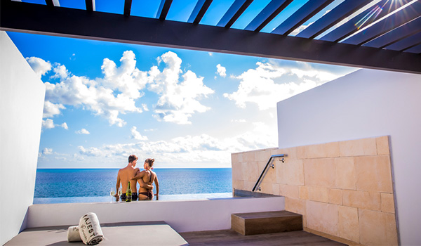 Couple sitting on the edge of a balcony infinity pool overlooking the ocean