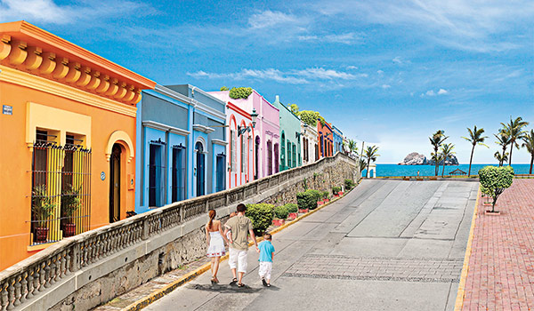 Family strolling down a coastal street lined with colourful houses