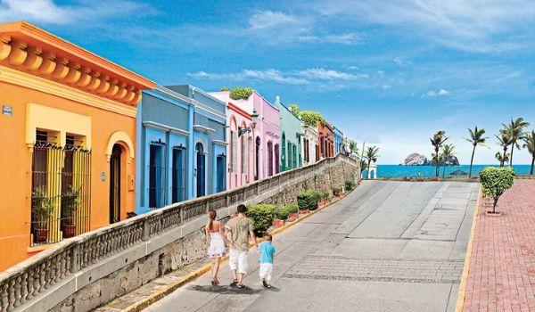Une famille se baladant le long d'une route bordée de la mer et dotée de maisons colorées