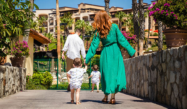 Family walking away towards the resort grounds along a stone path