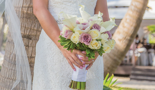 Bride holding a bouquet of purple roses and alcatraces