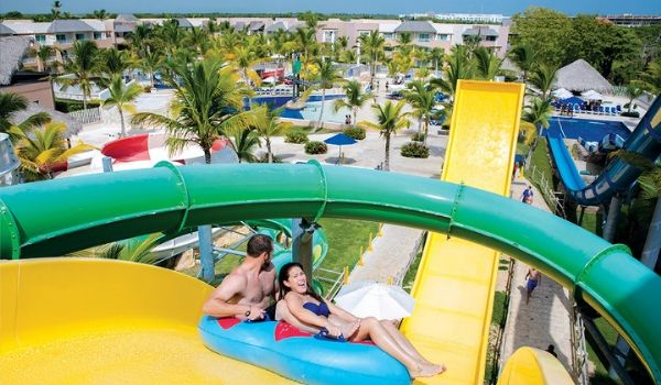 Man and woman going down water slide