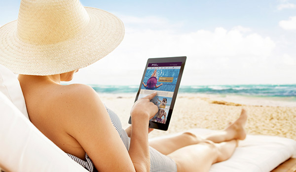 Woman sitting on a luxurious beach lounger reading an iPad