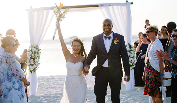 Bride and groom walking down an aisle on the beach