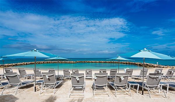 Plage au sable blanc bordée par des chaises longues et des parasols