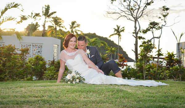 Bride and groom posing in a lush garden surrounded by palm trees