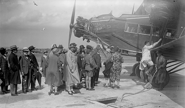 Black and white image of group of people getting on an old plane