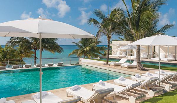 Piscine entourée de chaises longues confortables donnant sur la plage