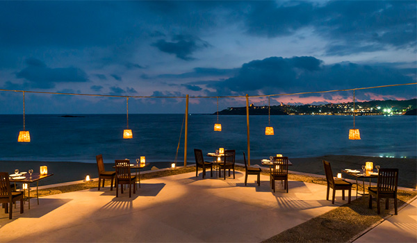 Set tables on a terrace overlooking the ocean at night with lanterns