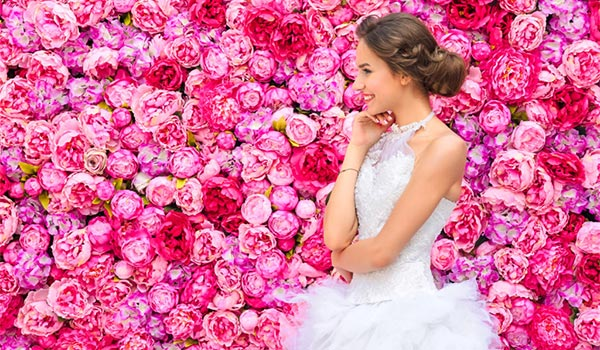 Bride standing in front of a wall covered in pink peonies and roses