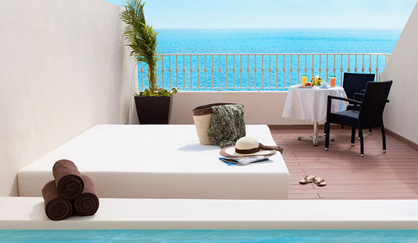 Bali bed and small table set with breakfast on a rooftop overlooking the ocean