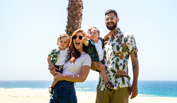 Mom, dad and twin babies standing underneath a palm tree by the beach smiling