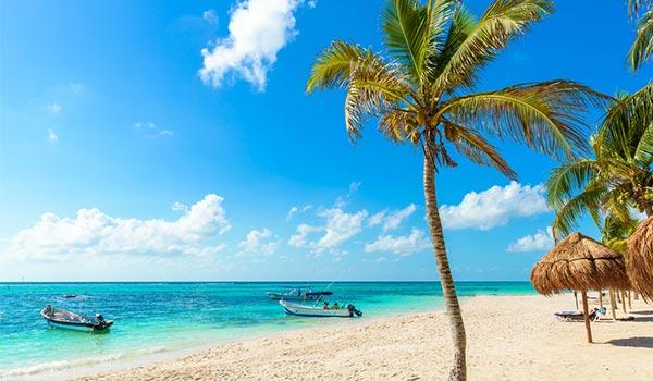 Palmiers et palapas sur une plage immaculée, devant deux bateaux amarrés dans l'eau