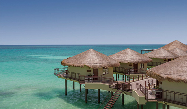 Charming bungalows sitting over the crystal-clear waters of the Caribbean Sea