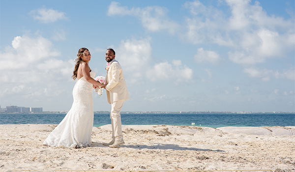 Sheniqua and Ejaz holding hands on the beach