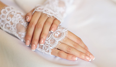 Woman posing wearing a lace dress with a French manicure
