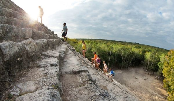 People climbing the steep ruins of a Mayan ruin