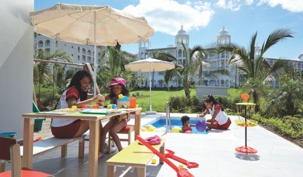 Enfants assis près d'une mini table de billard avec des employés de l'hôtel jouant à des jeux