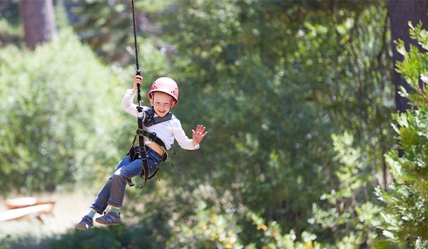 Little boy waving and ziplining through a forest