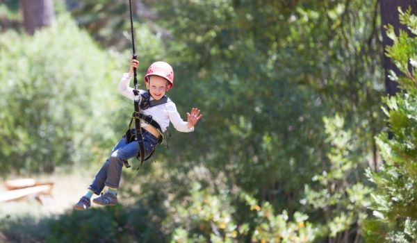 Little boy waving and ziplining through a forest