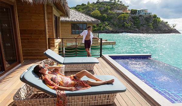 Couple lounging on the pool deck of their overwater bungalow