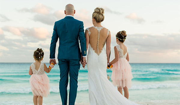 Vickie and Daniel holding hands with their daughters looking out at the ocean