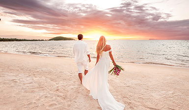 Bride and groom walking on the beach at sunset