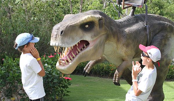 Deux enfants à côté d'un Tyrannosaure Rex anamatronique