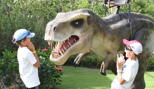 Two kids standing next to an animatronic T-rex