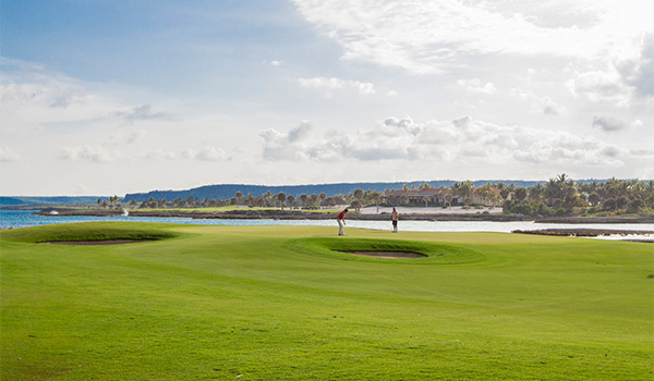Two people playing golf on a course overlooking the ocean