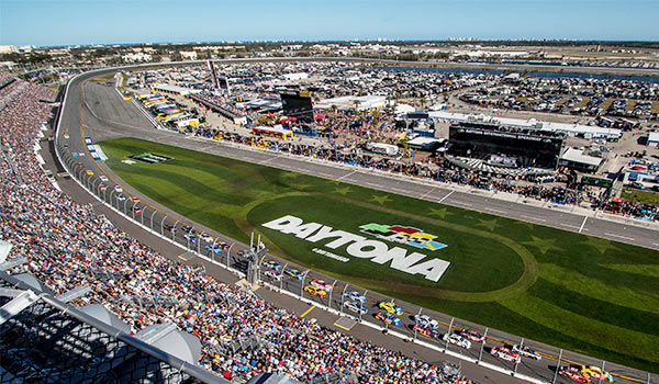 Aerial view of the Daytona Internal Speedway with colourful race cars and hundreds of spectators.