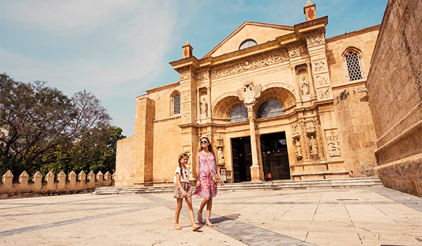 Mother and daughter walking through a historic square