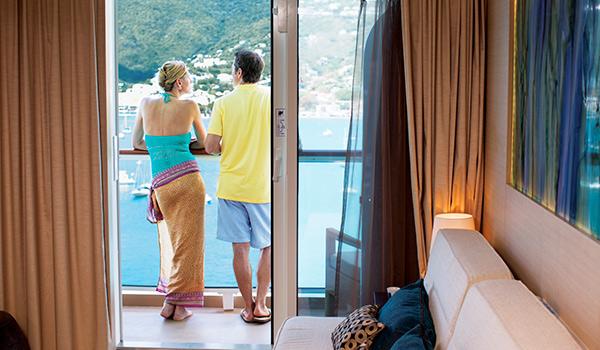 Couple se tenant sur le balcon de leur cabine avec vue sur la mer