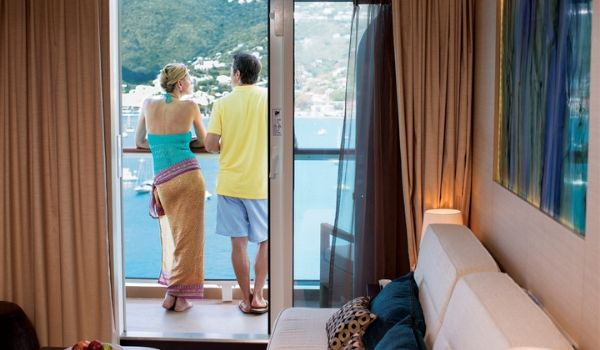 Couple standing on their stateroom's oceanview balcony