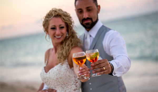 Bride and groom toasting with champagne glasses on the beach