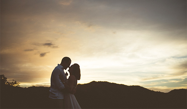 Bride and groom posing on the beach at sunset