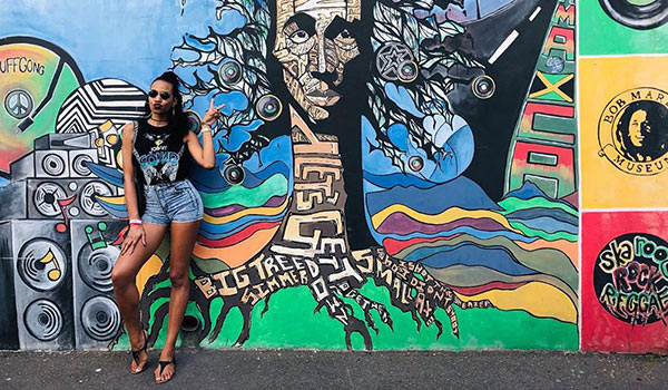 Girl posing in front of a Bob Marley mural