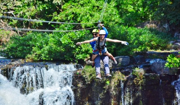 Two people tandem ziplining over a waterfall