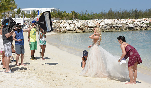 Liz having her photo taken on the beach surrounded by a production crew