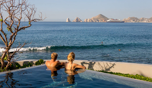 Couple sitting in an infinity pool overlooking the ocean and the rocky arches of Los Cabos