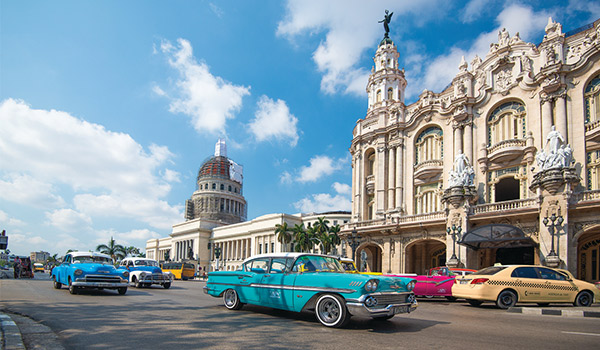 Classic American cars driving past historic buildings in Old Havana