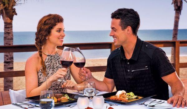 Couple portant un toast avec des coupes de vin en regardant la plage