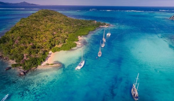 Aerial view of boats cruising past Tobago with the turquoise sea
