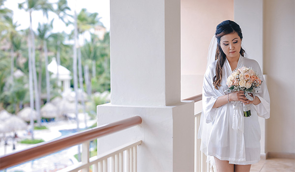 Bride getting ready on her hotel balcony, holding a bouquet of flowers