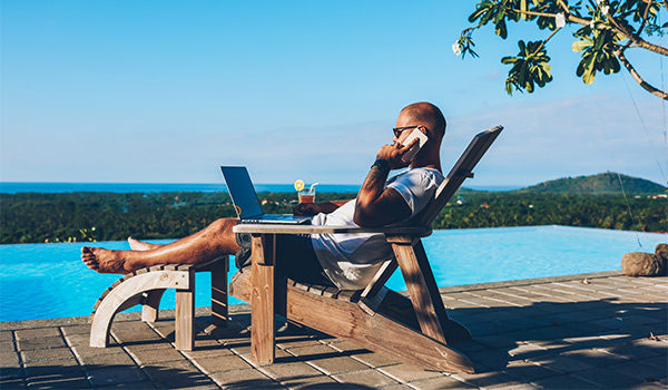 Man sitting by the pool working on his laptop