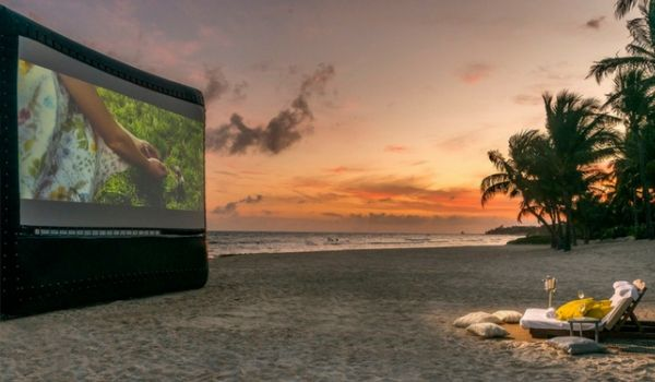 Movie screening on inflatable screen on the beach at sunset