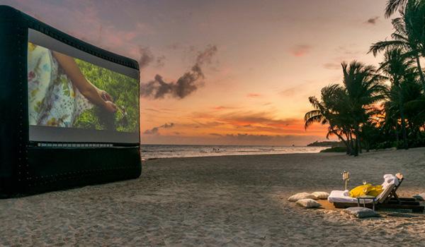 Écran gonflable sur lequel est joué un film sur la plage au coucher du soleil