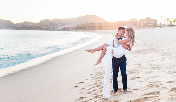 Groom carrying a bride along the beach at sunset