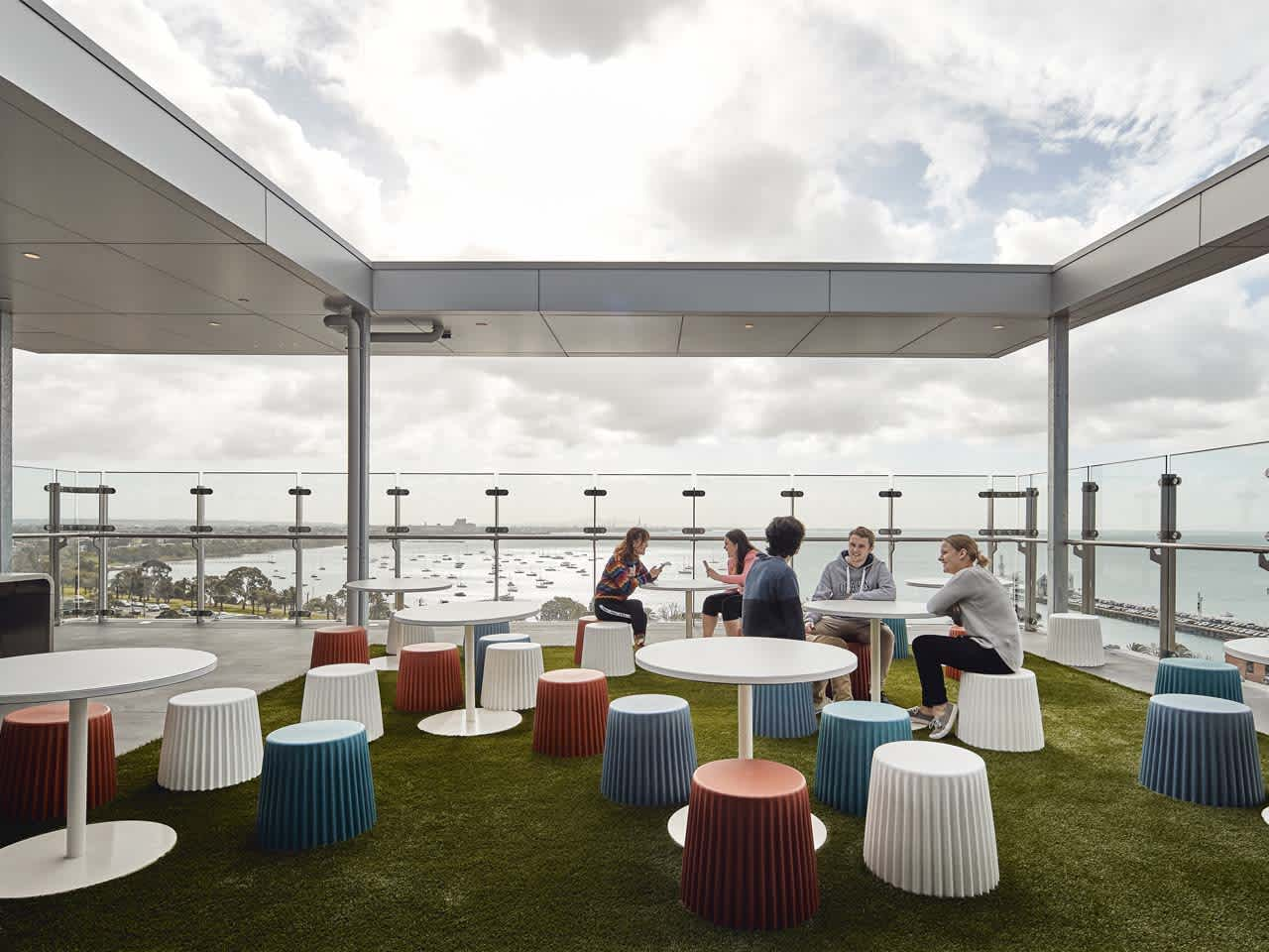 Students sitting on rooftop terrace looking over Geelong Waterfront