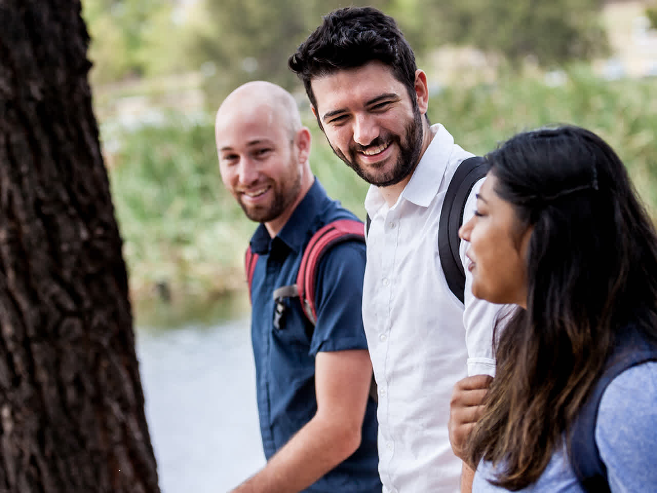 Three people walking and smiling, with trees in the background